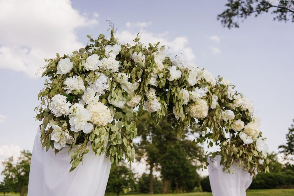 greenery and white flowers on wedding ceremony arch
