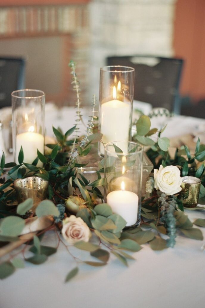 wedding centerpieces with candles in pillar vases and greenery